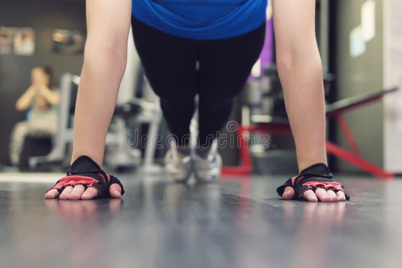 Sluit omhoog hand van vrouw die duw UPS in de gymnastiek doen Opleidende meisjes in de zaal Gloved handen op de vloer in close-up stock foto's