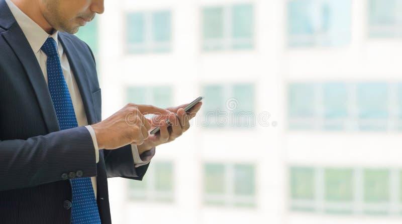 Sluit omhoog hand van zakenman gebruikend mobiele telefoon dichtbij bureauwind royalty-vrije stock afbeelding