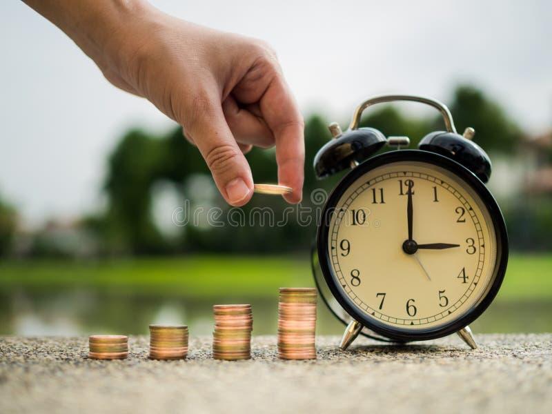 Sluit omhoog hand zettend geld aan stapel muntstukken met tijd, tijdwaarde van geldconcept in bedrijfsfinanciënthema Besparingsge royalty-vrije stock afbeelding
