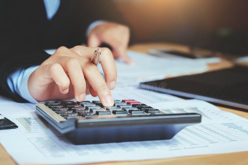sluit omhoog handaccountant gebruikend calculator met laptop concept s stock afbeeldingen