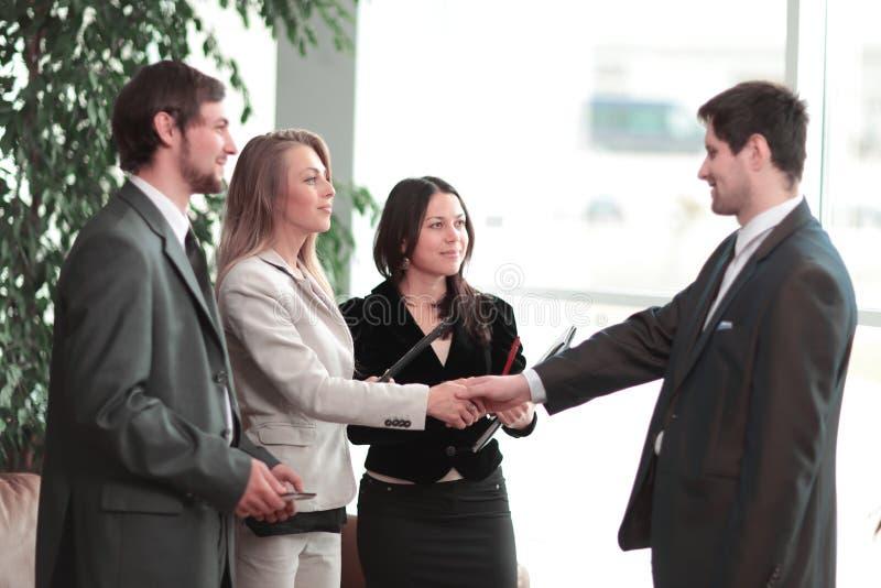 Sluit omhoog handdruk bedrijfsvrouw met zakenman in modern commercieel centrum royalty-vrije stock afbeeldingen