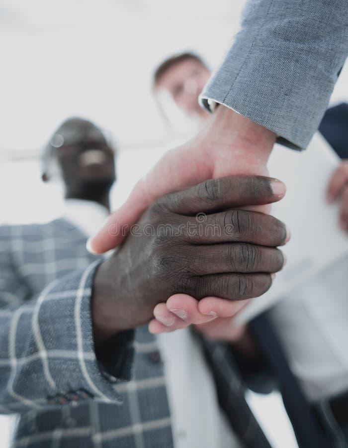 Sluit omhoog Handdrukpartners in het bureau stock afbeelding