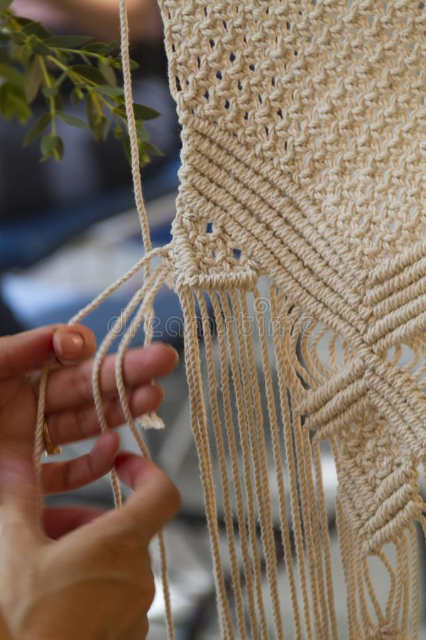 Sluit omhoog Handen die macramétapijtwerk met beige draad weven stock foto's