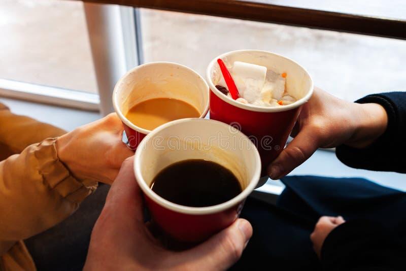 Sluit omhoog handen met koffiekoppen in toejuichingentijd de vrienden hebben pret en drinken koffie in de cafetaria royalty-vrije stock fotografie