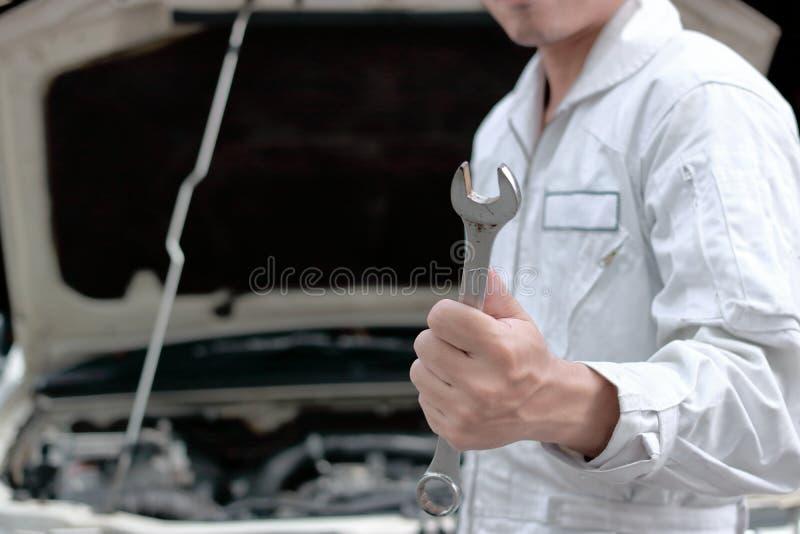 Sluit omhoog handen van de professionele jonge mechanische moersleutel van de mensenholding met auto in open kap bij de garageach royalty-vrije stock afbeeldingen