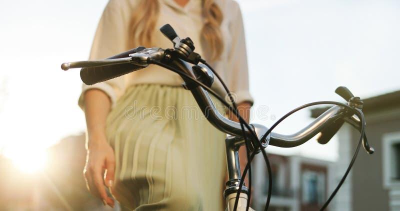 Sluit omhoog handen van een jong meisje op uitstekende fiets in park royalty-vrije stock foto