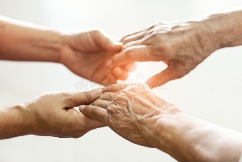 Sluit omhoog handen van het helpen van handen bejaarde thuiszorg Moeder en dochter stock foto