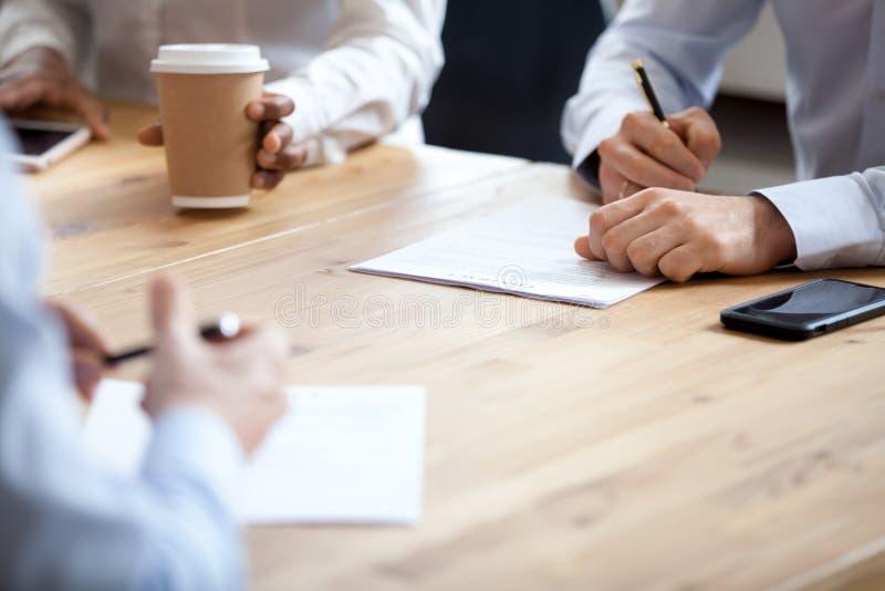 Sluit omhoog handen van partners die contract ondertekenen stock afbeeldingen