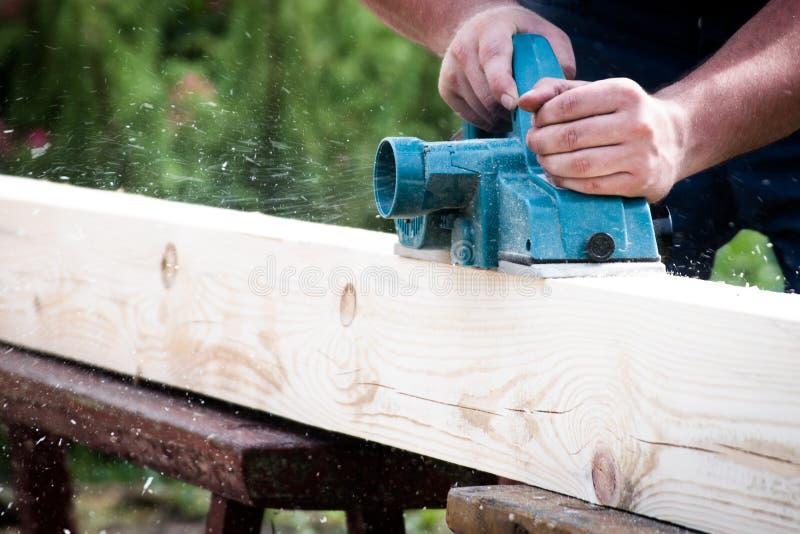 Sluit omhoog handen van timmerman die met elektrische planer aan houten plank werkt royalty-vrije stock afbeelding