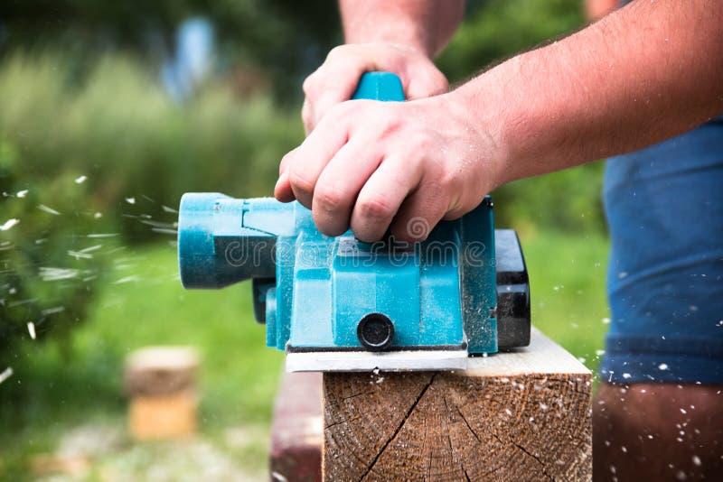 Sluit omhoog handen van timmerman die met elektrische planer aan houten plank werkt stock afbeelding