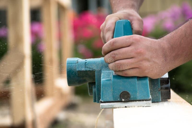 Sluit omhoog handen van timmerman die met elektrische planer aan houten plank werkt royalty-vrije stock foto