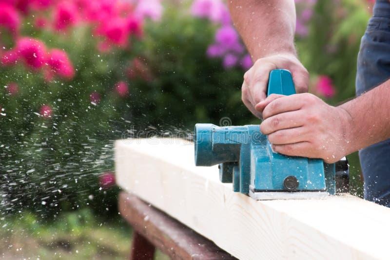 Sluit omhoog handen van timmerman die met elektrische planer aan houten plank werkt stock afbeeldingen