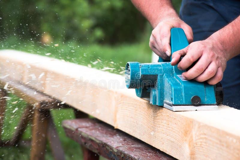 Sluit omhoog handen van timmerman die met elektrische planer aan houten plank werkt royalty-vrije stock fotografie