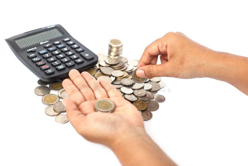 Sluit omhoog handtelling het muntstuk met calculator op witte B wordt geïsoleerd die royalty-vrije stock afbeelding