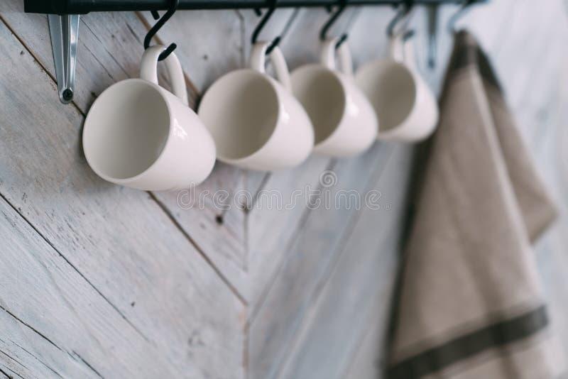Sluit omhoog, hangen vier witte koppen en de vage handdoek op haken op keukenmuur royalty-vrije stock afbeelding