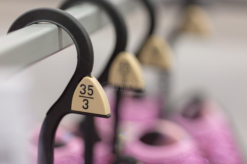 Sluit omhoog hangers die de verschillende Europese markeringen van de kledingsgrootte tonen stock afbeelding