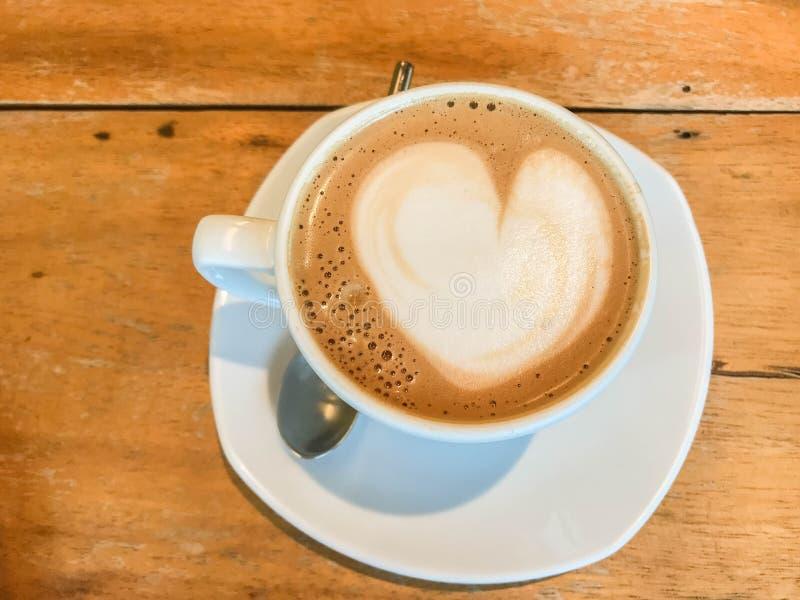 Sluit omhoog hartvorm van lattekunst op hete koffiekop op houten lijst in koffie royalty-vrije stock fotografie