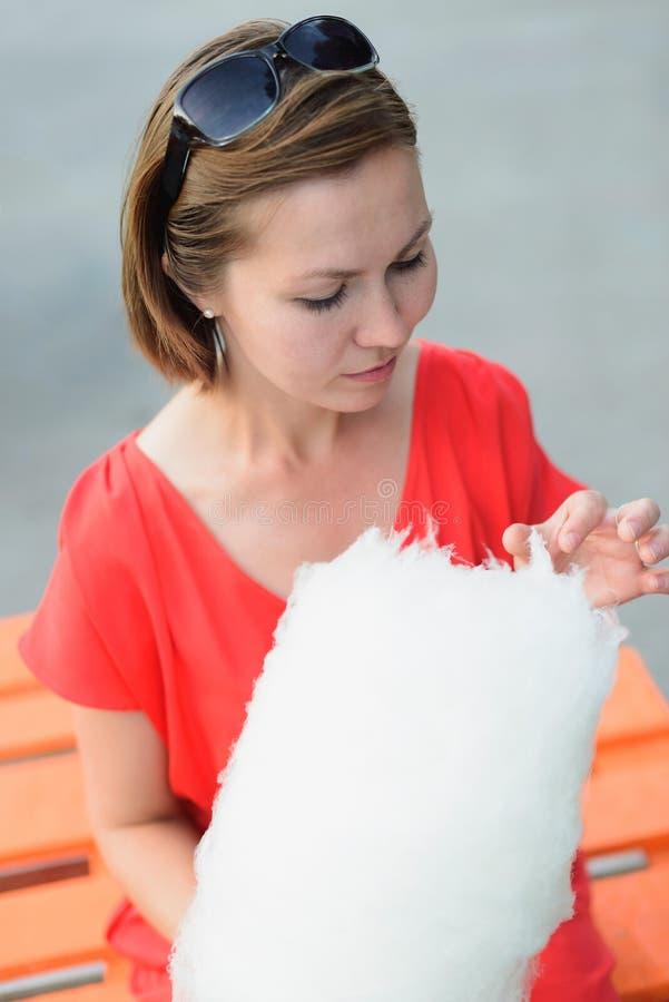 Sluit omhoog headshot van jonge volwassen vrouw in rode kledingszitting op bank met gesponnen suiker royalty-vrije stock afbeelding