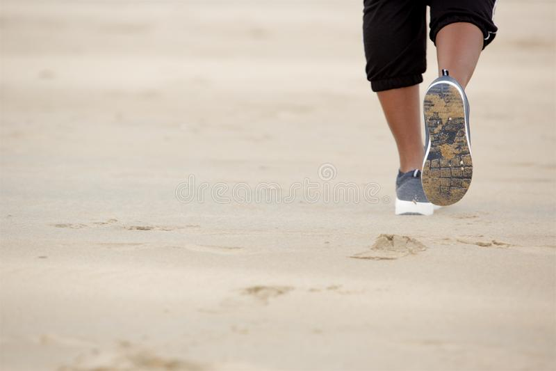 Sluit omhoog het Afrikaanse Amerikaanse vrouw lopen op zand bij het strand royalty-vrije stock fotografie
