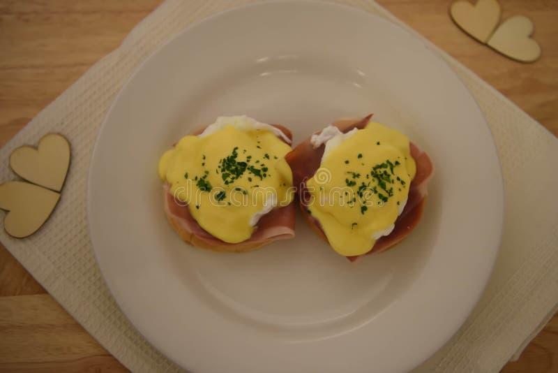 Sluit omhoog het beeld van de voedselfotografie van gediend ontbijt van eieren Benedict met muffinbacon en hollandaise saus op ho stock afbeelding