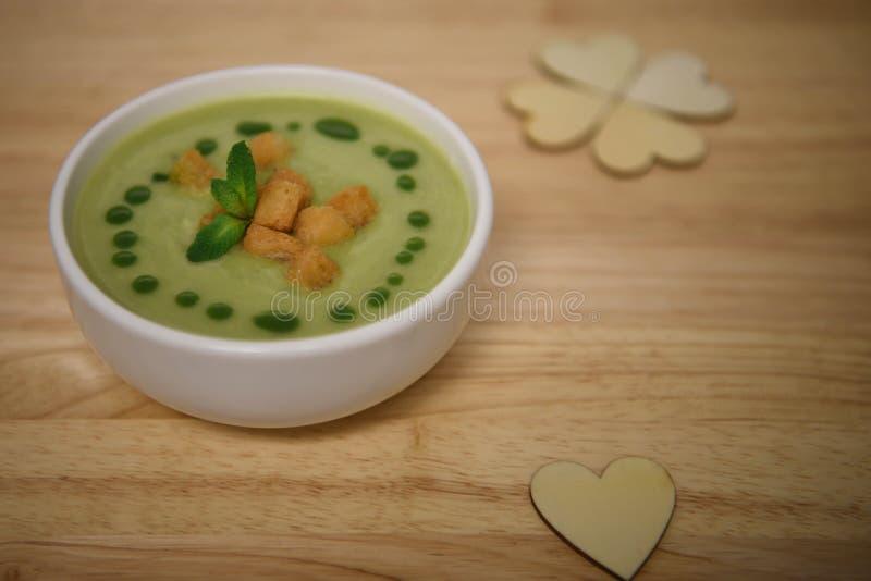 Sluit omhoog het beeld van de voedselfotografie van hete gekookte groene groentesoep met croutons en de houten decoratie van het  stock foto
