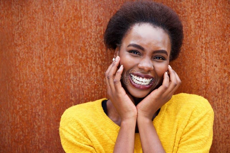 Sluit omhoog het gelukkige Afrikaanse Amerikaanse vrouw lachen tegen bruine roestachtergrond royalty-vrije stock fotografie