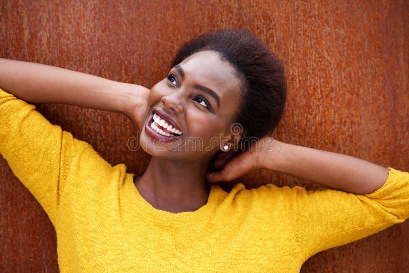 Sluit omhoog het gelukkige jonge zwarte glimlachen met handen achter hoofd tegen bruine achtergrond stock foto