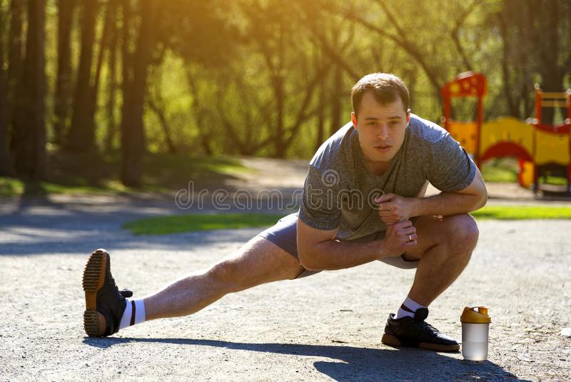 Sluit omhoog het gezonde Kaukasische atleten uitrekkende benen vooruitzien Knappe mens met fles die water in bos dichtbij uitoefe stock afbeeldingen