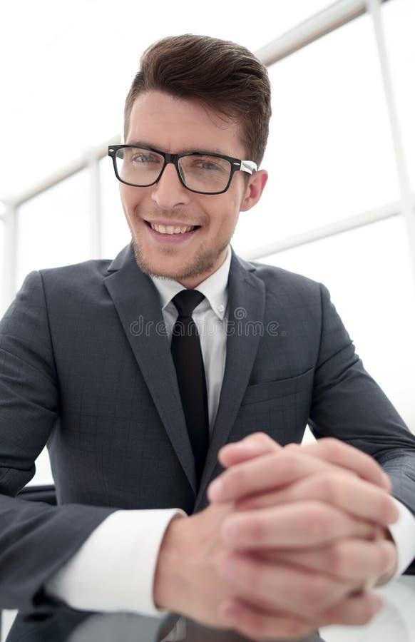 Sluit omhoog Het glimlachen zakenmanzitting bij zijn bureau stock fotografie