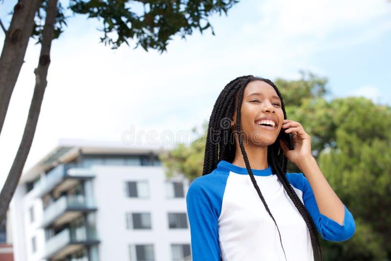 Sluit omhoog het jonge Afrikaanse vrouw lopen in openlucht en het spreken op telefoon stock afbeeldingen