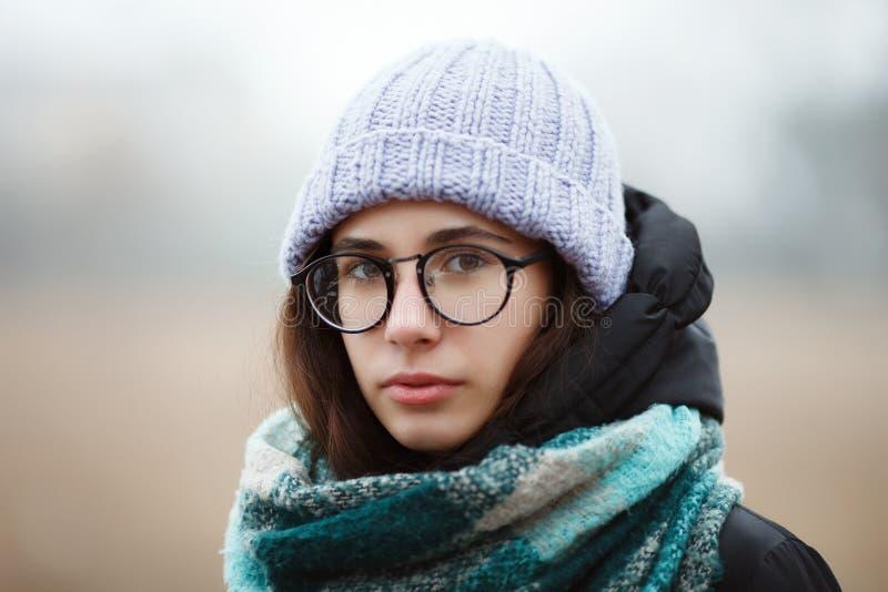 Sluit omhoog het jonge leuke donkerbruine meisje die van het de winterportret de winter bospark wandelen stock afbeeldingen