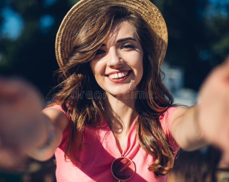 Sluit omhoog het lachende meisje die van portretnice in hoed selfie op het strand maken Het leuke portret van de de zomermanier v stock foto's