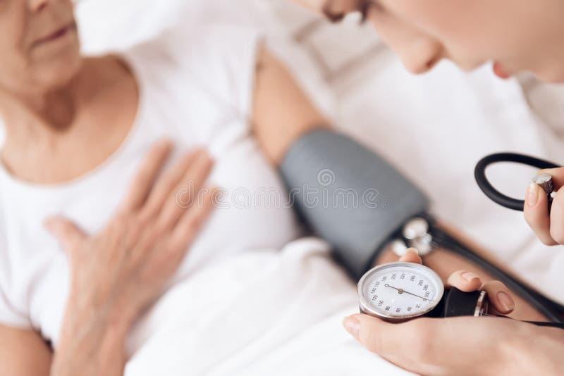 Sluit omhoog Het meisje geeft thuis voor bejaarde Het meisje gebruikt tonometer om bloeddruk te meten royalty-vrije stock afbeelding