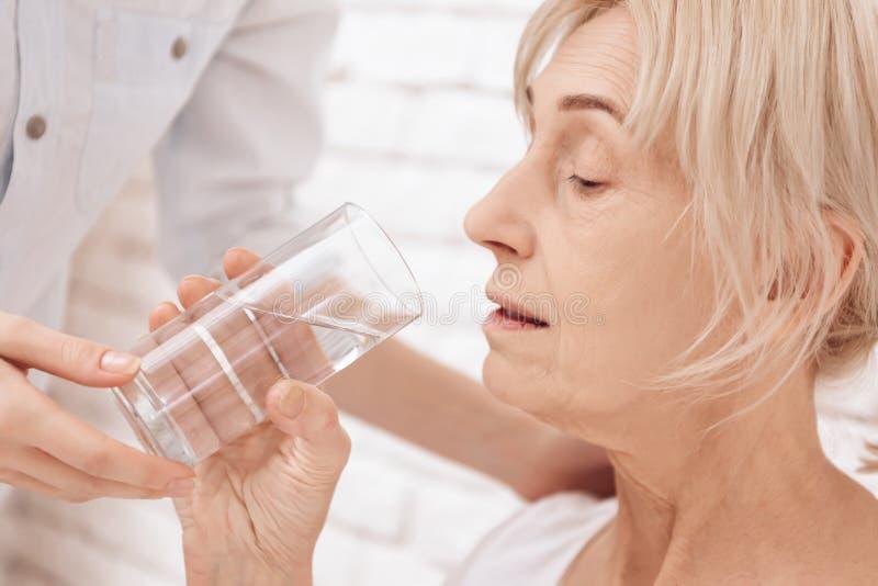 Sluit omhoog Het meisje geeft thuis voor bejaarde Het meisje helpt vrouw met glas water stock afbeelding