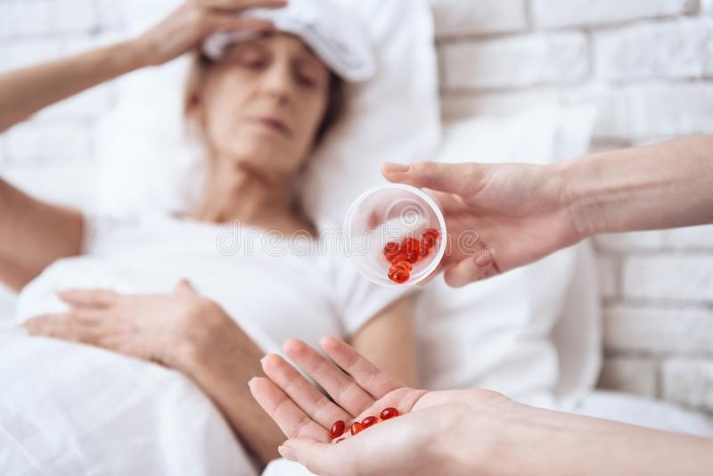 Sluit omhoog Het meisje verzorgt thuis bejaarde Rode pillen in kop voor vrouw stock afbeelding