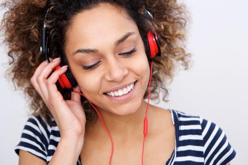 Sluit omhoog het mooie jonge Afrikaanse Amerikaanse vrouw luisteren aan muziek met hoofdtelefoons stock foto's