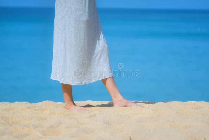 Sluit omhoog het mooie jonge vrouwelijke voeten blootvoetse lopen op zandstrand met overzeese en hemelachtergrond De ochtend oefe royalty-vrije stock afbeelding