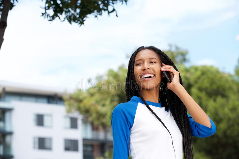 Sluit omhoog het mooie zwarte meisje in openlucht lopen en het spreken op celtelefoon stock foto