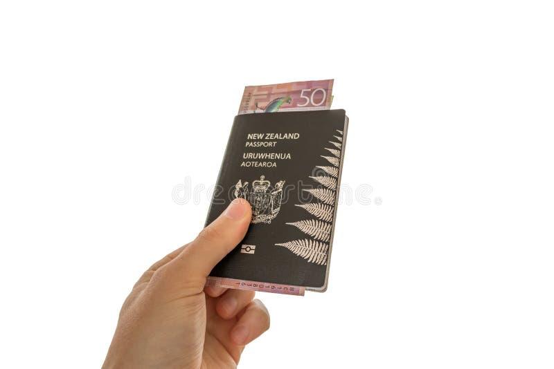Sluit omhoog het Paspoort van Nieuw Zeeland met Geld die worden gehouden stock afbeelding