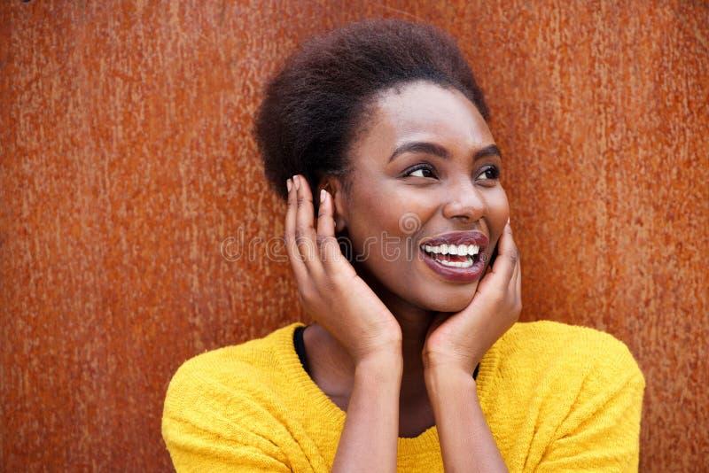 Sluit omhoog het zekere jonge zwarte glimlachen tegen bruine achtergrond stock foto