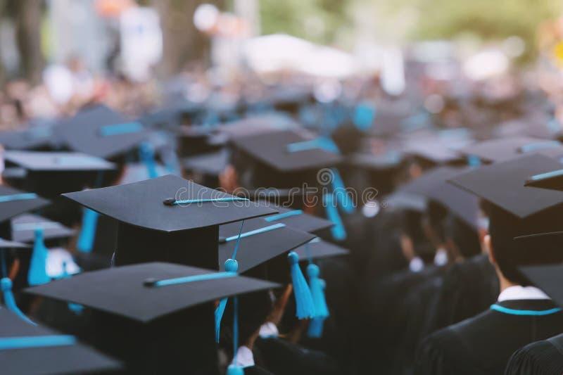 Sluit omhoog hoedengroep Gediplomeerden tijdens begin De gelukwens van het conceptenonderwijs stock foto's