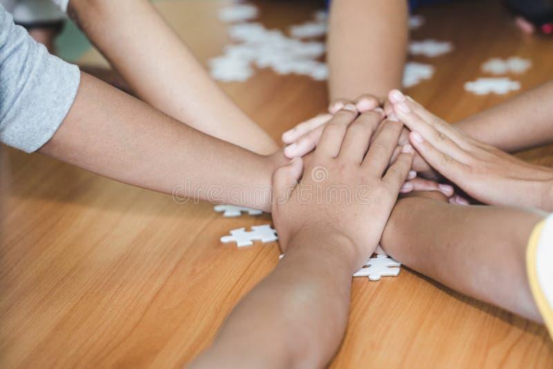 Sluit omhoog hoogste mening van jongeren die hun handen samenbrengen Vrienden met stapel handen die eenheid en groepswerk tonen royalty-vrije stock foto