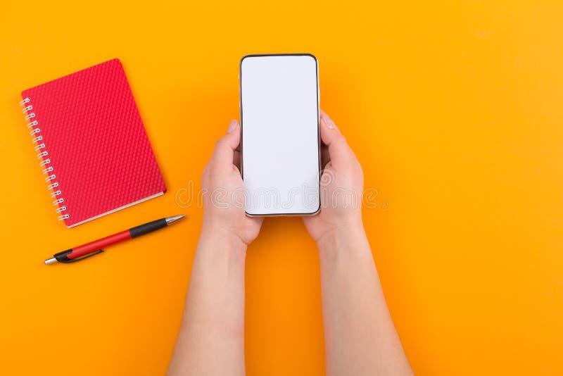 Sluit omhoog hoogste mening van vrouw die een smartphone met het lege scherm, notitieboekje en pan op oranje achtergrond houden stock foto's