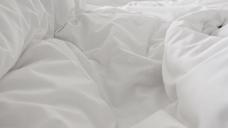 Sluit omhoog hoogste mening van wit hoofdkussen op bed en met rimpel slordige deken in slaapkamer stock foto