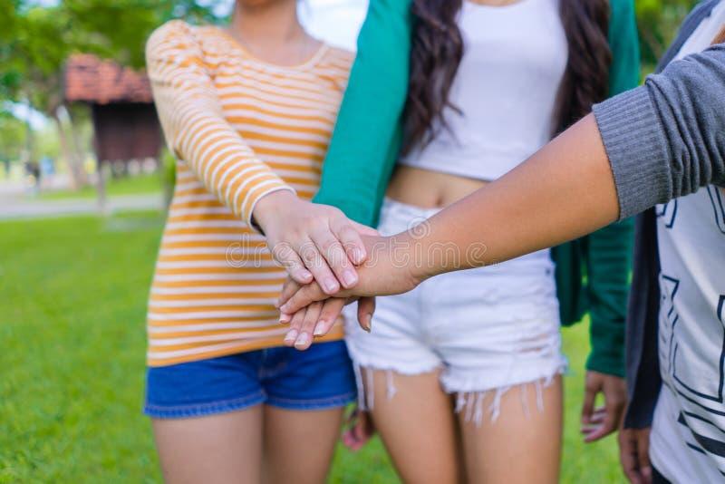 Sluit omhoog hoogste meningsgroep jonge tienermensen die handen samenbrengen Vrienden met stapel handen die eenheid en groepswerk stock fotografie