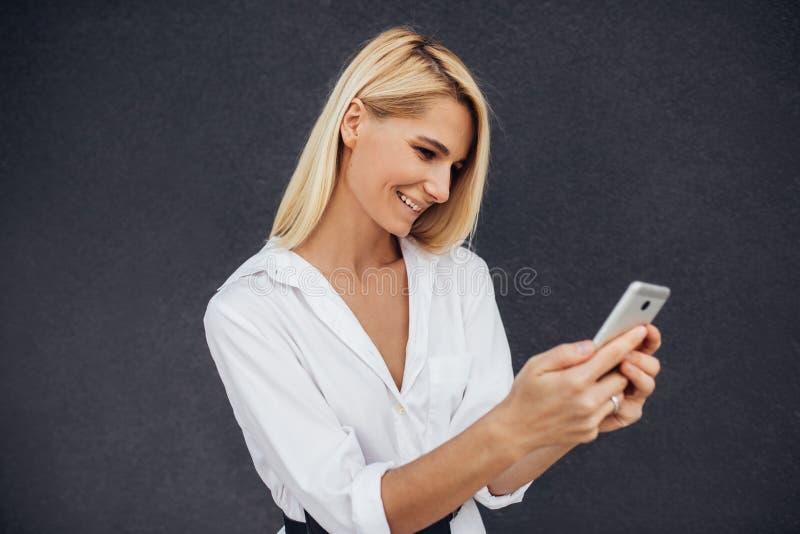 Sluit omhoog horizontaal portret van mooi Kaukasische jonge vrouwelijke lezend of texting sms-bericht bij het mobiele telefoon st royalty-vrije stock fotografie