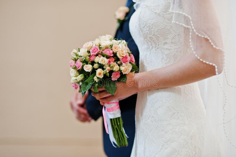 Sluit omhoog huwelijksboeket van kleine rozen dichtbij van bruid stock foto