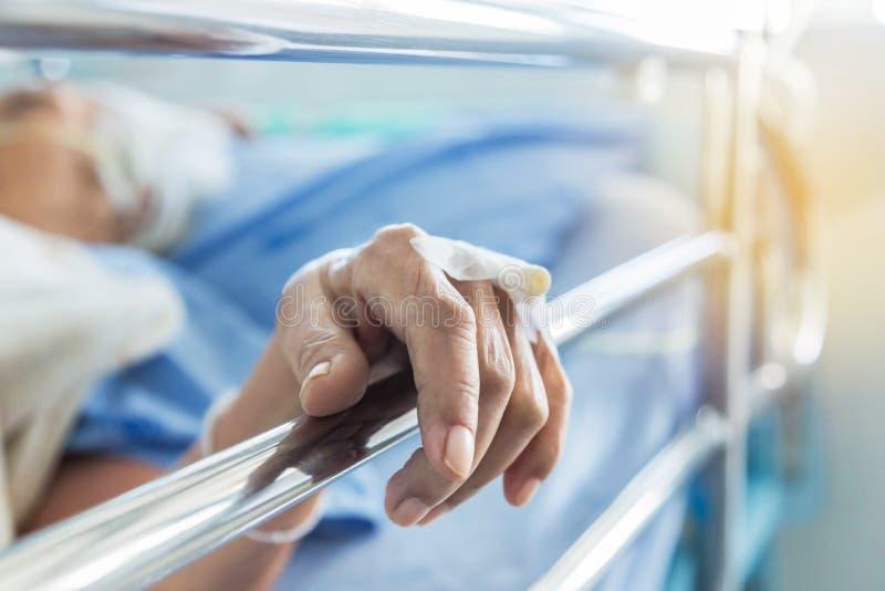 Sluit omhoog intraveneuze catheter voor injectiestop ter beschikking van bejaarde patiënt liggend in het ziekenhuis stock fotografie