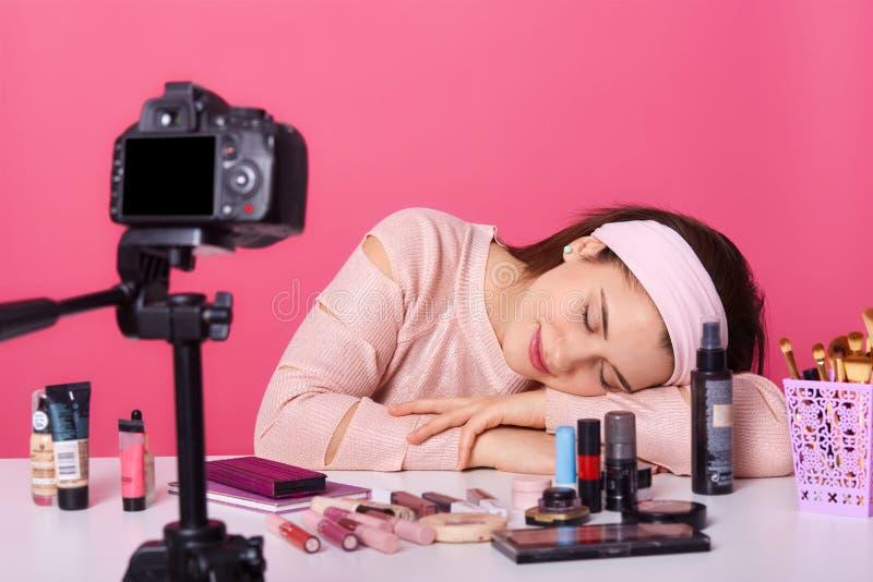Sluit omhoog jong wijfje blogger, kijkt vermoeid, in slaap dalingen terwijl het registreren van nieuwe video op camera, advertere stock afbeelding