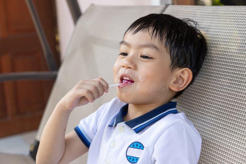 Sluit omhoog jonge Aziatische jongen die een lolly eten royalty-vrije stock foto